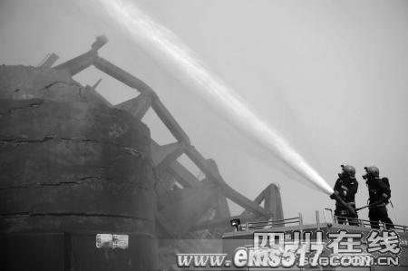 爆破后,消防队员冲水洗尘